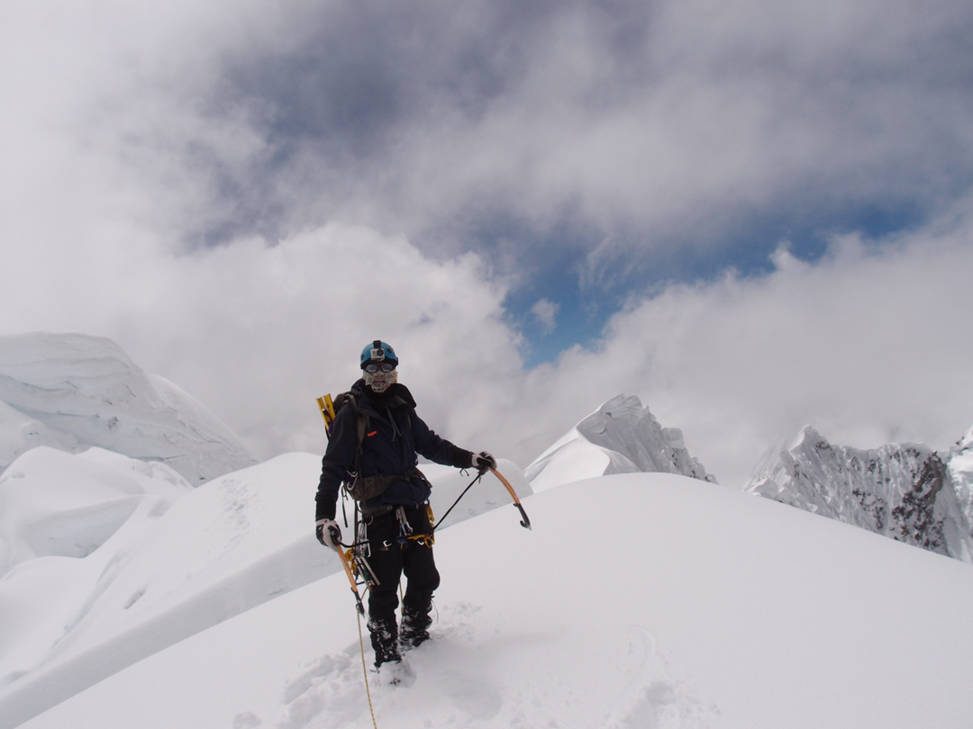 Nathan Heald descending from the summit as clouds build.
