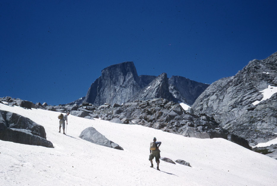 The first ascent team approaches the Merlon (the large, left-leaning tower) in 1961. The east face of Cloud Peak is visible behind and right.