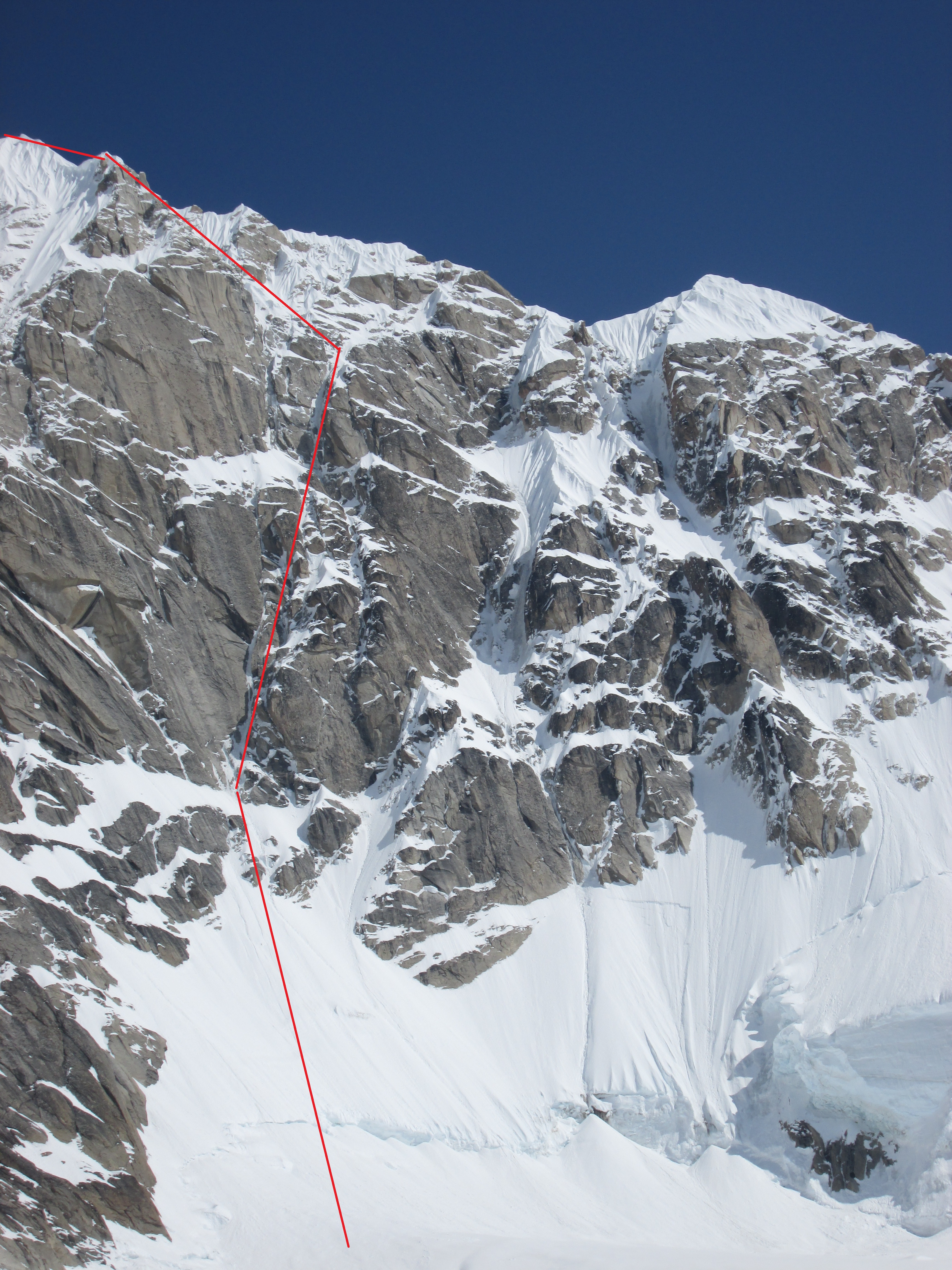 "A foreshortened view of the west face of Peak 13,100', ""Reality Peak,"" as seen from the pocket glacier below. Devil's Advocate (4,200', AI5 M4) follows the red line."