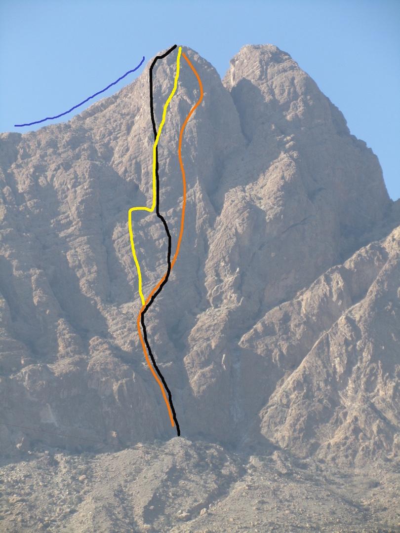 Approximate lines of the three known routes on the northeast face of Jebel Ghul. Black line: Original Route (650m, VII, Davison-Hornby-Sammut, 2002). Yellow line: A Trois Sans Vin Dans la Tour (VII+, Christophel-Rigaut-Toutan, 2006). Orange line: Italian Route (650m, 6b+, Migliano-Schiera, 2013). The blue line shows the 2002 descent route.