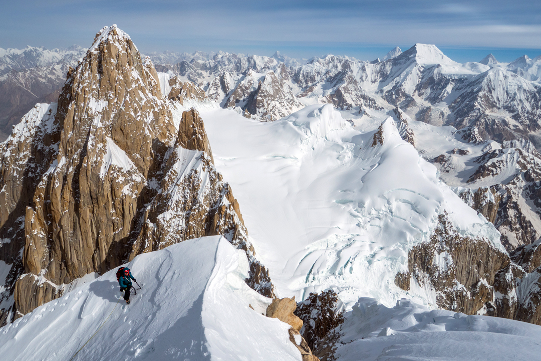 Andy Houseman on the summit ridge of Link Sar West, with K7 directly behind. Below and right is the K7 Glacier. The prominent trapezoidal snow peak is Chogolisa, with K2 just behind and left and Gasherbrum IV just to the right.