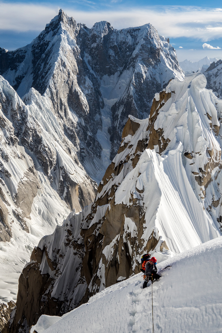Andy Houseman on the summit ridge of Link Sar West with the north face of K6 behind (from left to right: main summit, unclimbed central summit, and west summit).