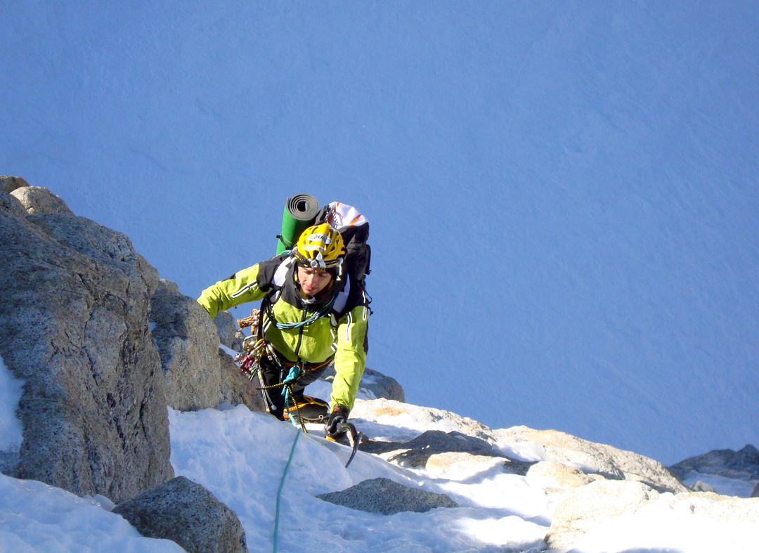Marco Farina emerging from the mixed ground of the initial rock buttress onto the great snow and ice slope.