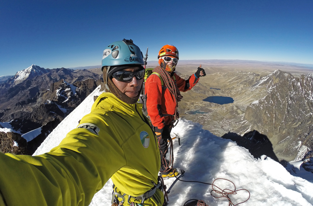 Juvenal (left, in yellow) and Sergio Condori on the summit of Wyoming (Huallomen) during their 44-hour traverse of the Condoriri Massif. Huayna Potosi is in the distance at left.