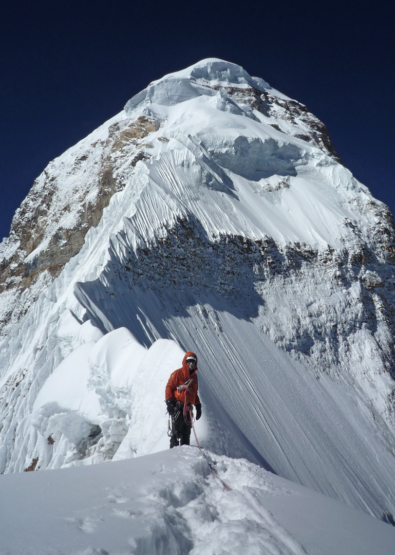 Martin Moran at the high point on the northeast ridge of Nanda Devi East, with the sharp, horizontal snow ridge that thwarted the attempt, and the summit pyramid, behind.