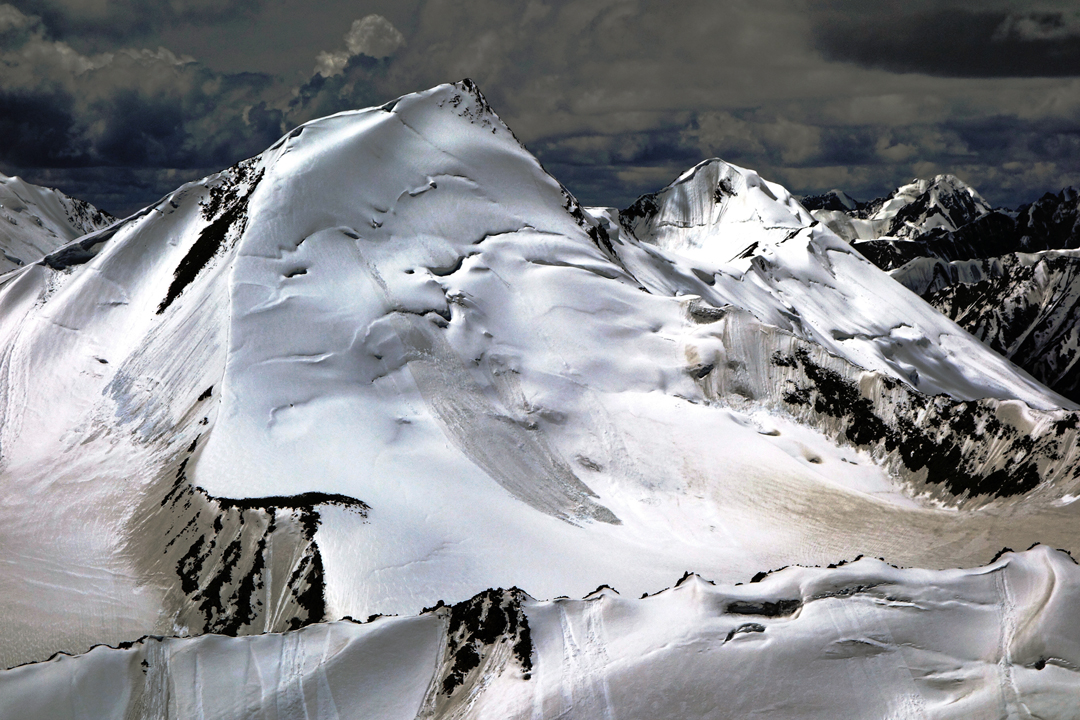 Seen to the southwest, Sagtogpa Kangri from the summit of Peak 6,195m. The team climbed from the far side to reach the upper section of the southeast ridge (left skyline), which they followed to the summit. Behind and right is Peak 6,215m (a.k.a. Pyramid Peak or X3), attempted by a British team in 2015 by the southeast ridge (left skyline).