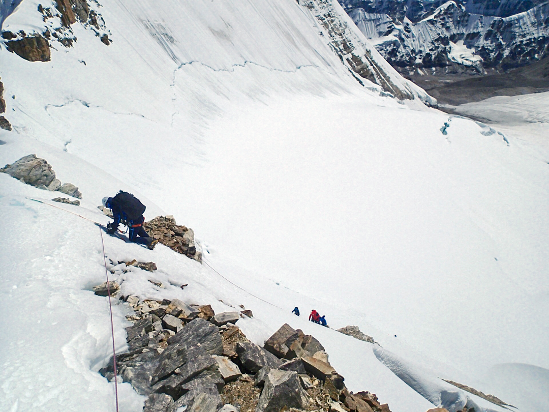 Climbing the final section of the south face of Dzanye II with the upper plateau of the  northwest branch of the Chijima Glacier below and the slopes of Lashar I behind.