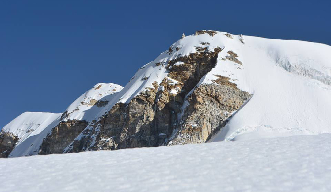 The final section of the south face of Dzanye II. The route climbed the snow slope left of the serac formation in three pitches.