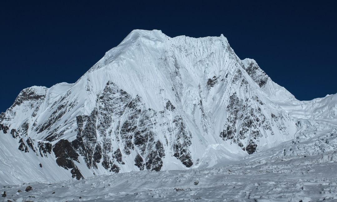 Praqpa Ri from the Savoia Glacier. The east-southeast ridge, attempted in 2016, is coming down toward the camera on the left from the southeast summit (7,026m). The main (middle) summit (7,156m) is the pointed top to the right, with the northwest summit (7,058m) visible behind. The flat-topped summit far left is Khalkhal North (6,820m).