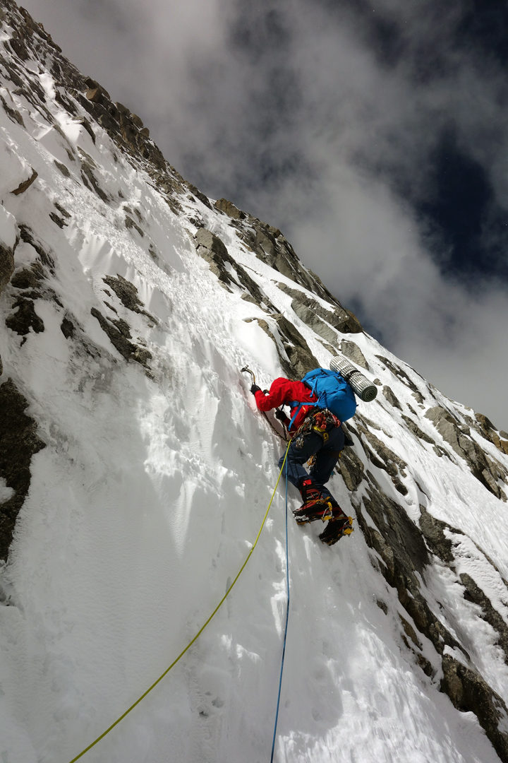 Domen Kastelic climbing steep snow and ice in the middle section of the northeast face of Pogolha/Jang Tsang Go (6,328m).