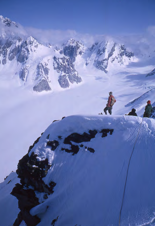 Joe Firey and George and Frances Whitmore take in the view from Peak 6,310', above the west side of the east fork of the Neacola Glacier. The view is to the southeast, toward Peak 6,925' and Peak 7,230' at the head of the glacier.