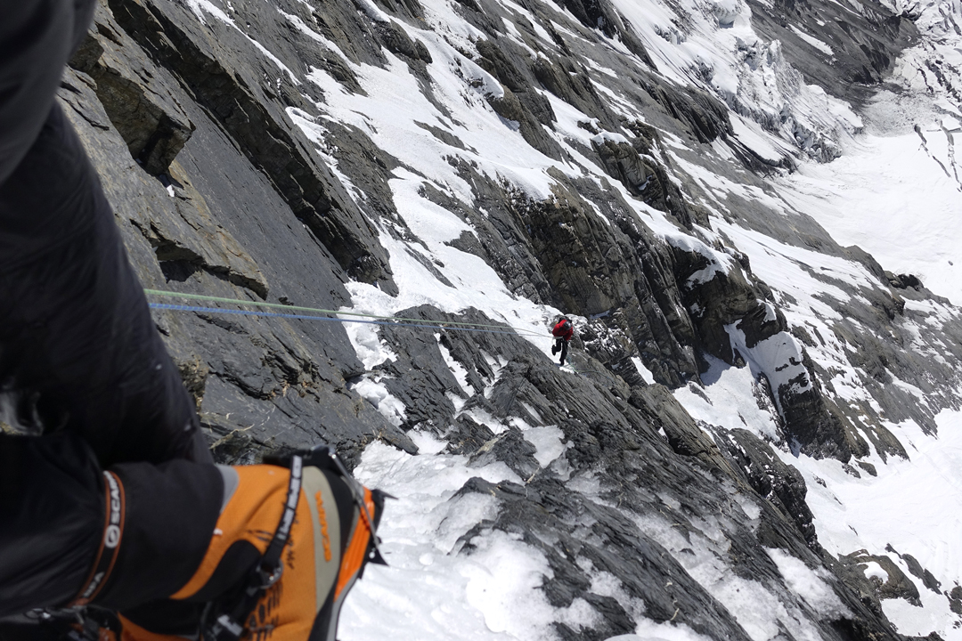 Rappelling through the rock barrier during the descent of the south face of Gangapurna.