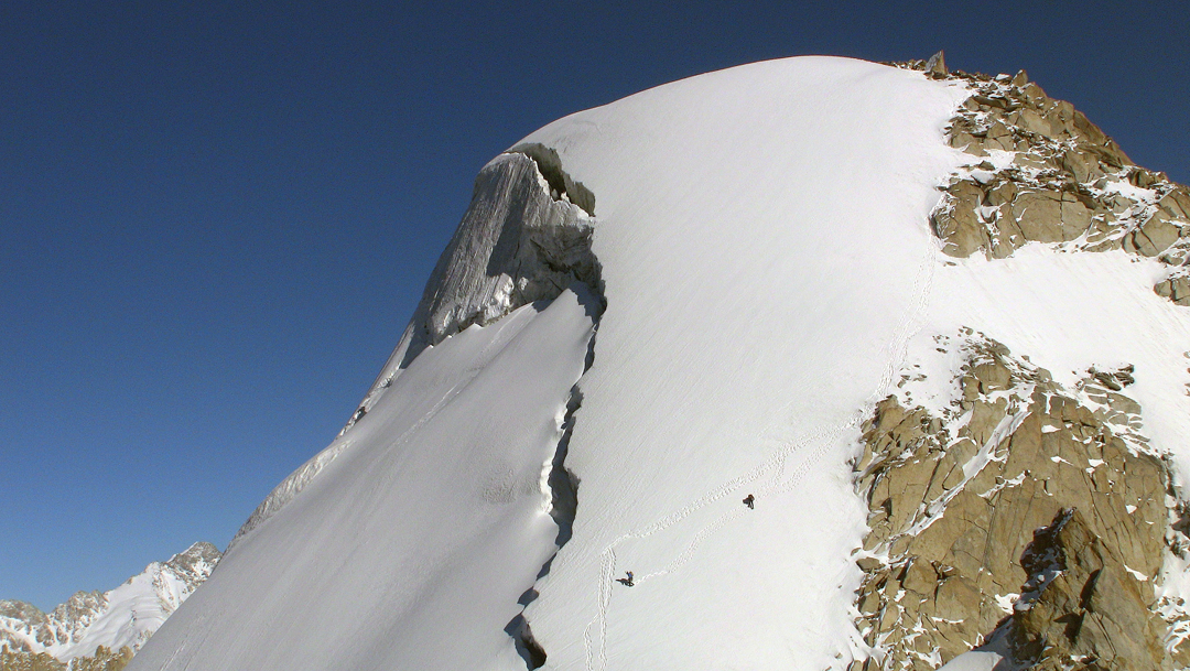 Descending the summit snow dome of Sickle.