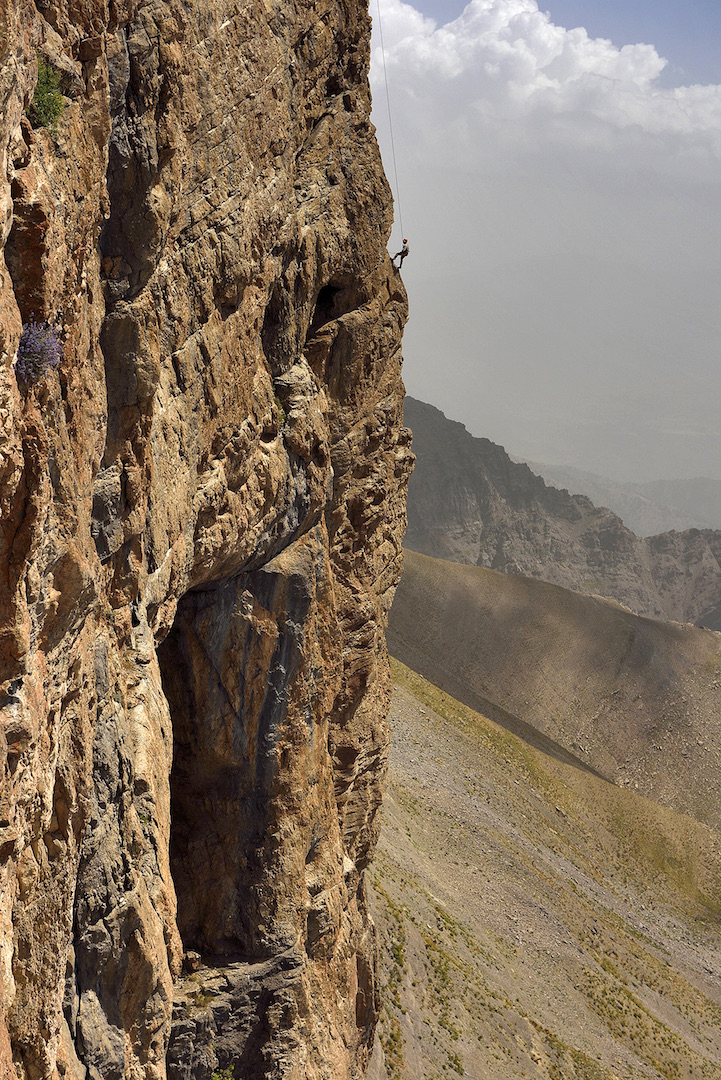 Mark Synnott rappelling the steep face of Hodja Gur Gur Ata, with entrances to the Dark Star caving system visible.