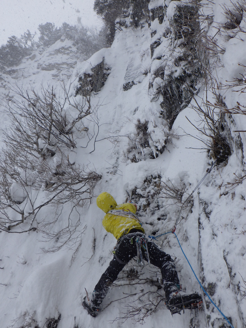 Yusuke Sato leading steep snow- and brush-covered rock on the ninth pitch of the Kurobe Golden Pillar.