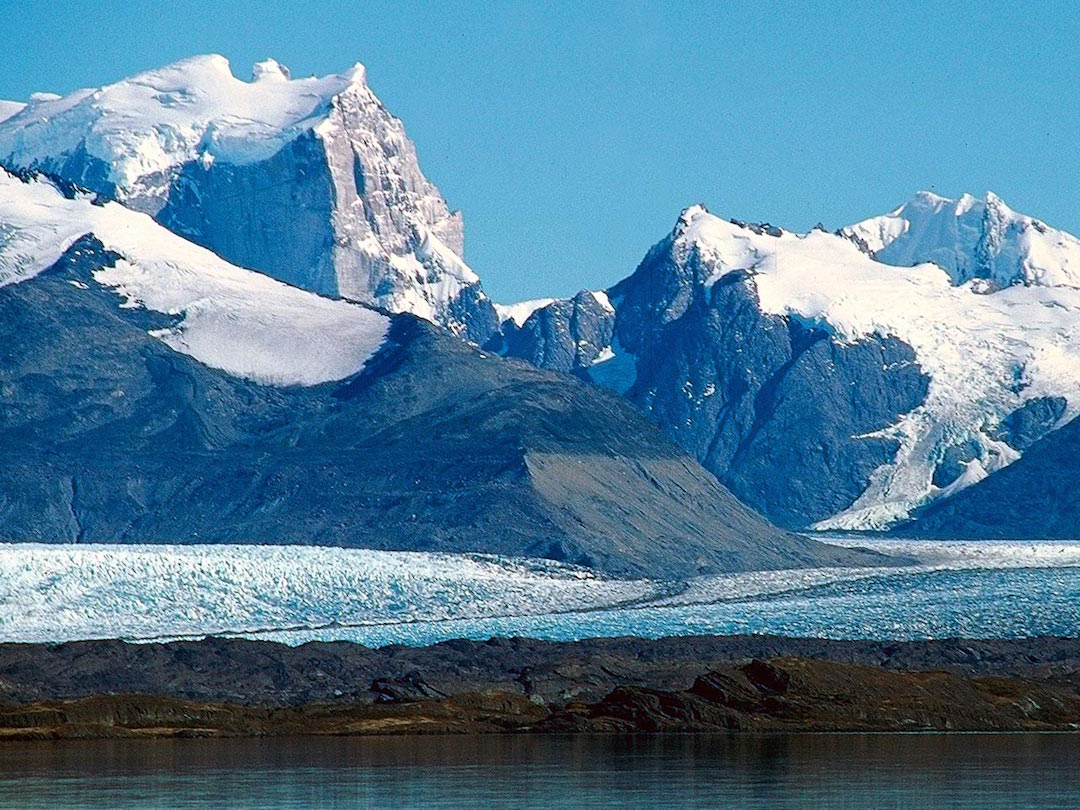 Cerro Murallón (left) from the Upsala Glacier. The east face is in the sun. The 2017 route up the east face and the 1984 ascent of the northeast arête both topped out on the east summit (farthest right). The 2017 team rappeled the wall at far left, under the seracs. At right, the highest peak is Cerro Don Bosco.
