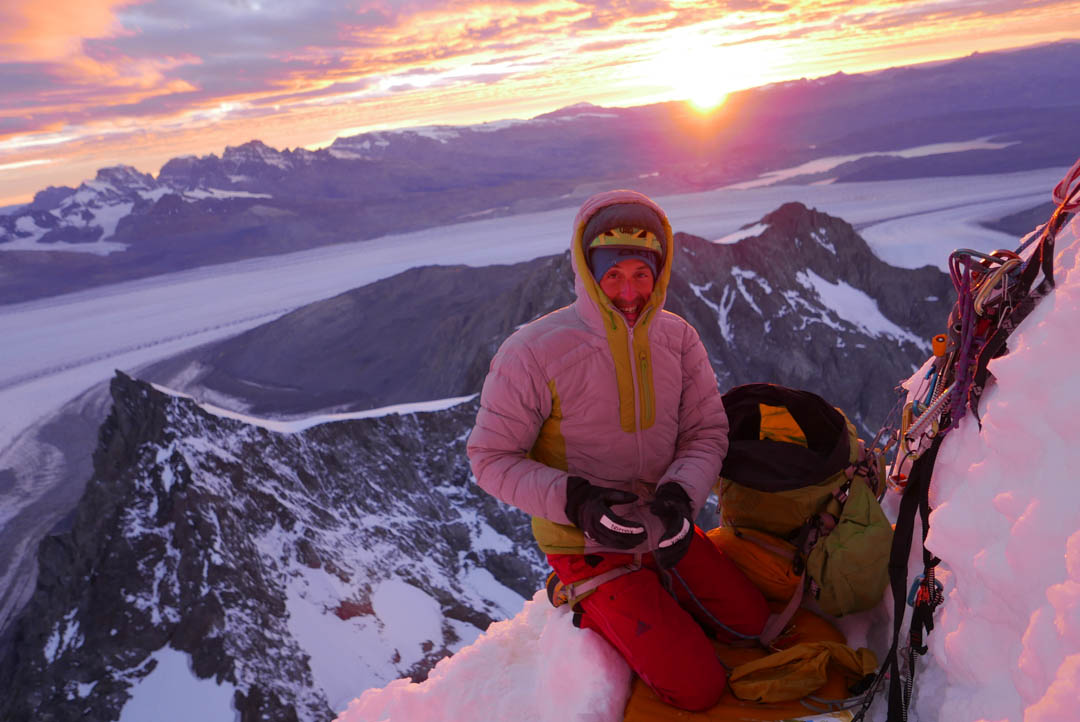 Matteo Della Bordella welcomes the sun, high on the east face, with the Upsala Glacier and Lago Argentino behind.