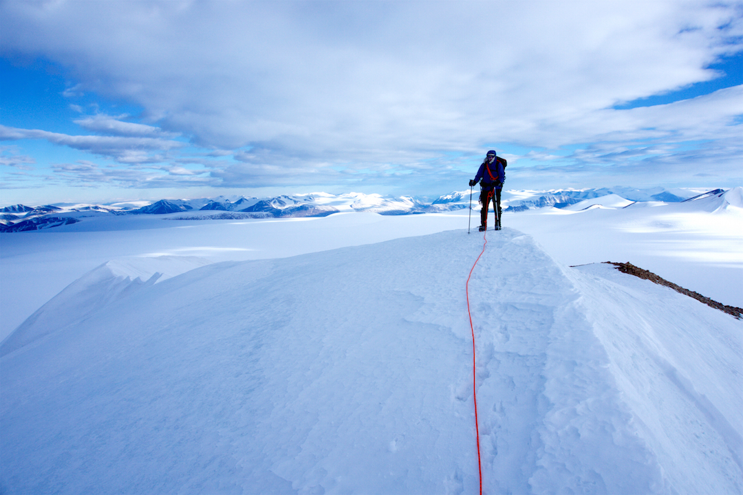 Eric Gilbertson on the summit of Peak 1,893m, looking south toward Tanquary Fjord in the distance, with the Adams Glacier below. The party's exit route followed the glacier to the left side of the picture.