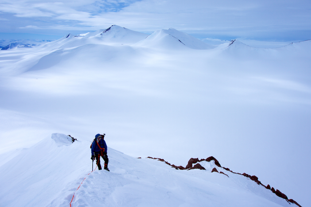 Eric Gilbertson ascending the southwest ridge of Peak 2,359m. Barbeau Peak is the highest one in the background, with Griper Peak just to the right of it and Peak 2,417m in front of Barbeau. Base camp is in the flat basin below.