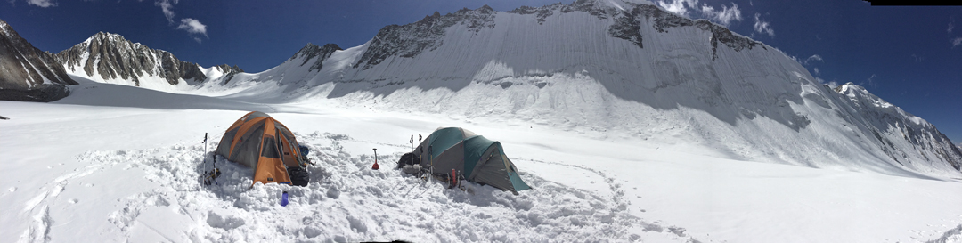 Camp at 5,680m on the more northerly of the two branches of the Sumur Glacier visited by the 2017 British expedition. The climbers ascended this glacier to summit Tsagtuk Kangri, off picture to the left. Deception Point (6,068m), climbed from the opposite side, is above and a little right of the green tent, with its top just off picture.