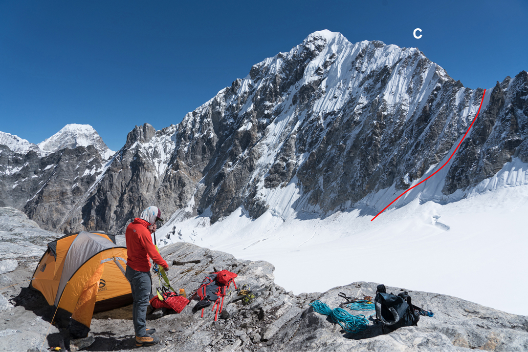 High camp on the south ridge of Peak 5,794m with Chugimago behind. The gully approach to the west-southwest ridge is marked, as is the 6,000m point (C) where the stove and rock gear were cached. For lines on the northwest face, see AAJ 2017.