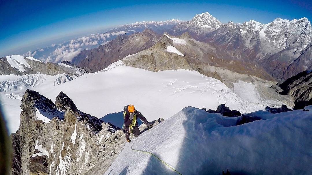 Kristoffer Erickson on the west-southwest ridge of Chugimago. The big peak in the distance is Gaurishankar, while the summit on the far right is Kang Nachugo. The foreground peak, across the glacier above Erickson, is Peak 5,794m.