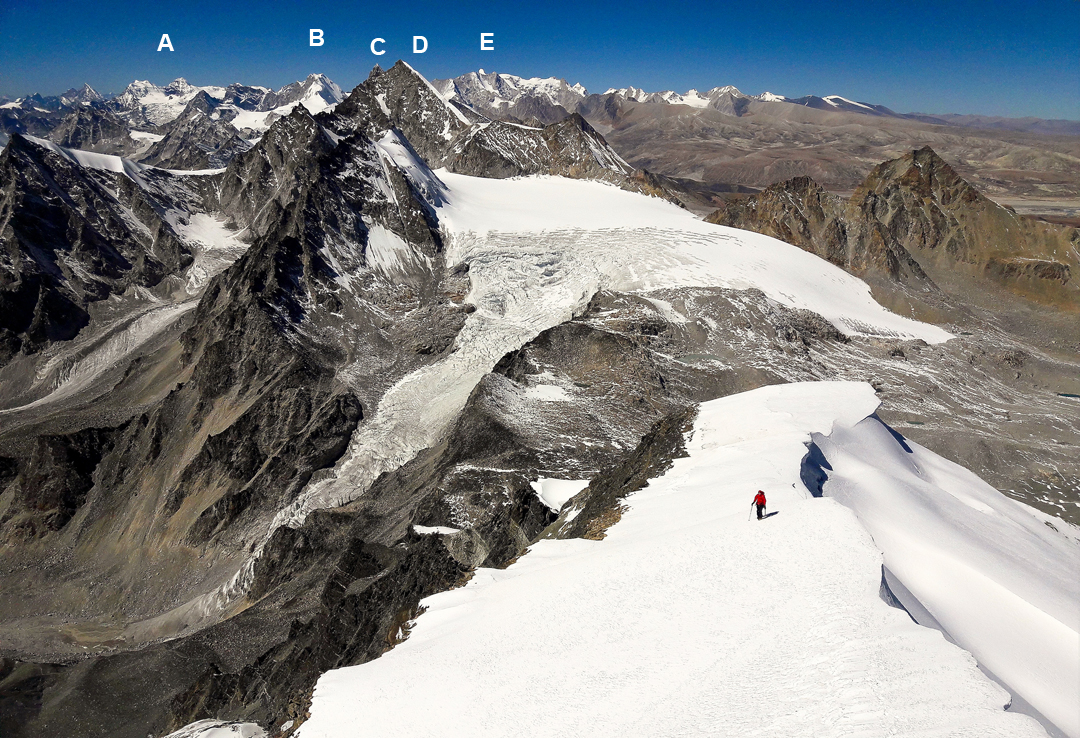 Franz Friebel on the northwest ridge of Pratibandhit Lek. The Kang La, below and behind, gives passage between Nepal (left) and Tibet (right). (A) Unnamed twin peaks at the head the Bholbihan Khola, the objective of a 2017 American expedition. (B) Asajya Tuppa (6,265m). (C) Absi (6,254m). (D) Kangla II (Ngomo Ding-Ding, 6,133m HGM Finn). (E) Lachama (a.k.a. Kubi Kangri, 6,721m).