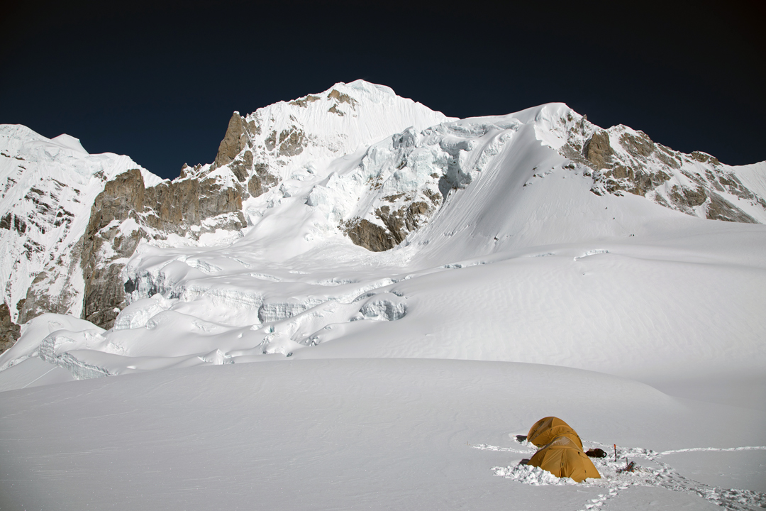 Camp 1 on Burke Khang. The summit is the highest point visible in the center of the picture, and Camp 2 was placed on the glacier shelf below and to the right. Climbers can be seen making their way up the lower part of the snow spur leading to the shelf. On the left is part of Hungchi.