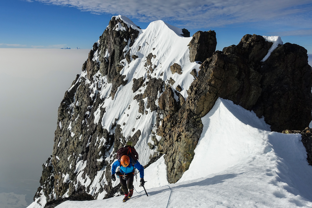 Micha Rinn traversing the summit ridge of Monarch Mountain after climbing Game of Thrones on the southwest face. The Waddington group is far in the background.
