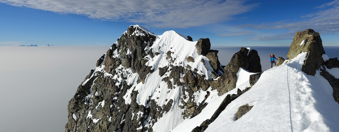 Micha Rinn traversing the summit ridge of Monarch Mountain after climbing Game of Thrones on the southwest face. The Waddington group in the distance.