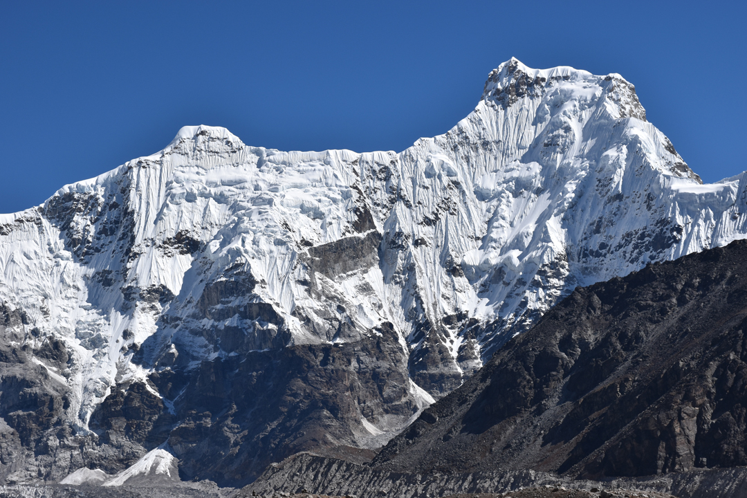 Hungchi from the Ngojumba Glacier to the southwest. The northwest ridge is the left skyline, and Tharke Kang is the obvious flat-topped summit. Hungchi was first climbed in 2003 by the southwest ridge, the upper part of which is visible on the right side of the image.