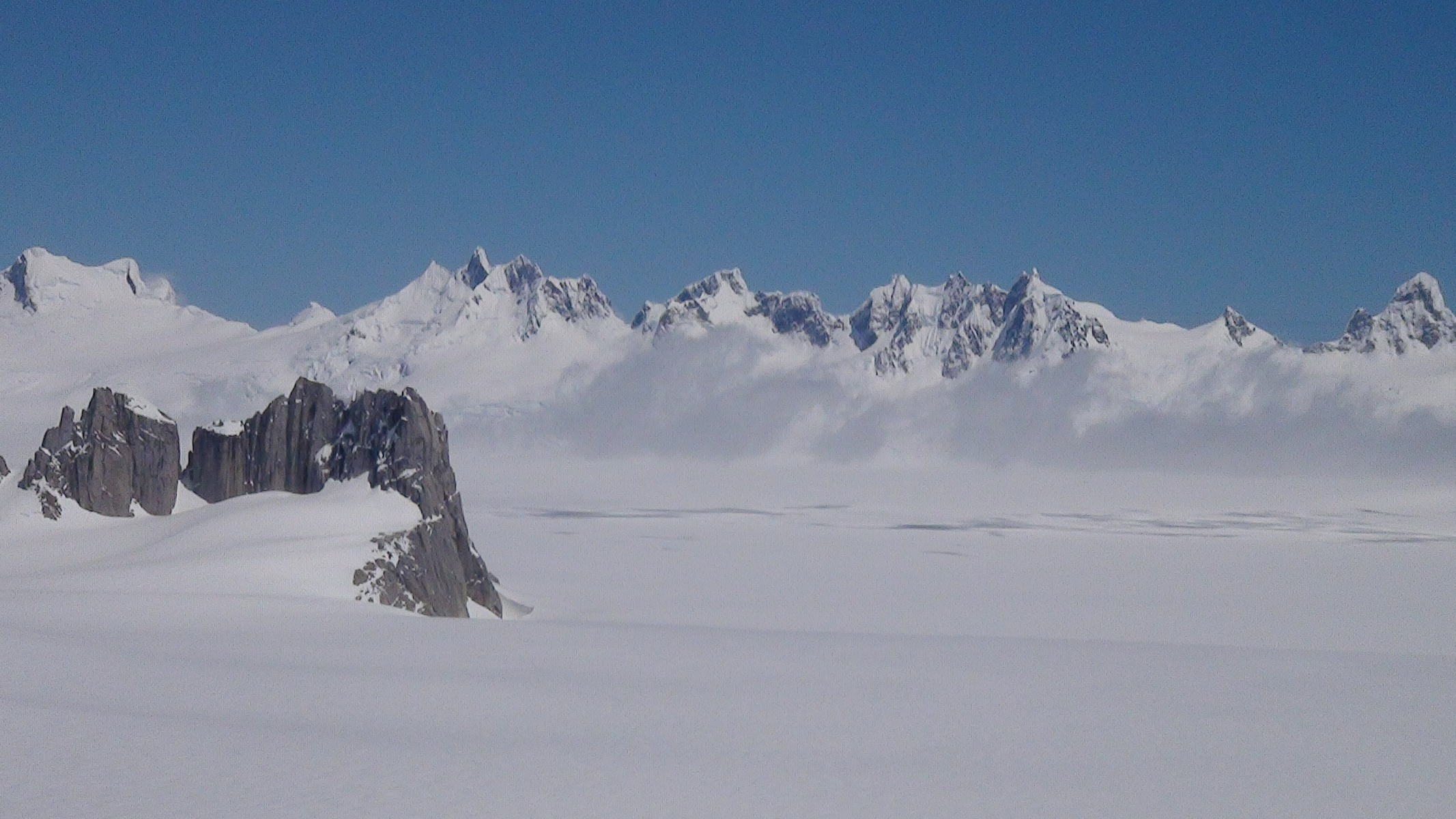 "Looking across to a chain of peaks on the west side of the Northern Patagonian Ice Field, which are most likely unclimbed. The small massif on the left with the spire-like main summit is known simply as A3 (the subsidiary summits continuing right down the skyline are A4 and A5, respectively); the attractive peak on the far right side is ""Alfil."""