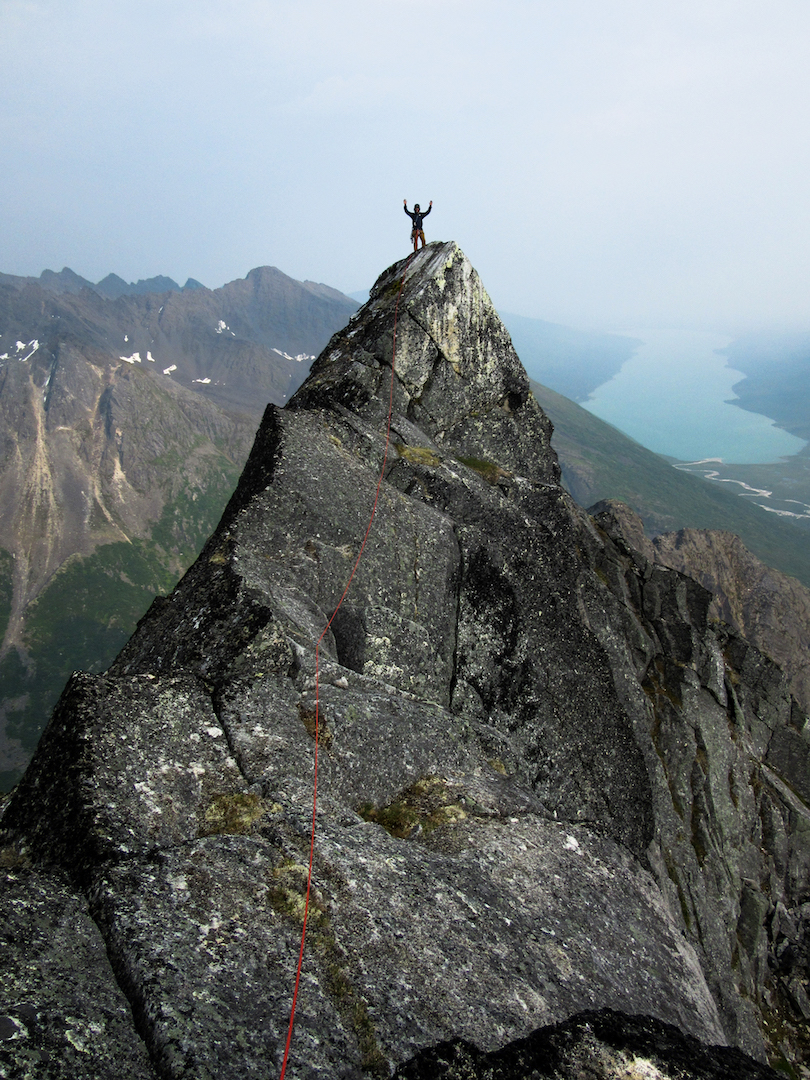 Zach Clanton on the summit of the Dogtooth after making the first ascent of the peak via the southeast ridge. Chelatna Lake is visible in the background.