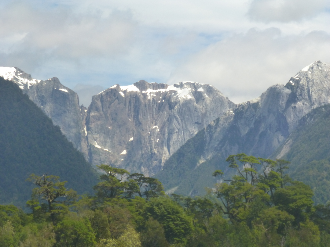 The east wall of El Trono/Serrania Avalancha, as visible from Carraterra Austral and Lago Yelcho. Both known routes climb the right half of the wall, which is obscured by a foreground hill.