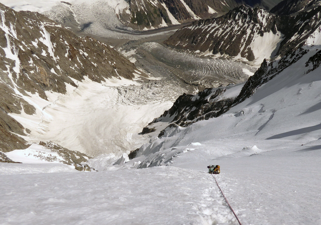On the long snow slopes of the southeast face of Jinnah Peak, looking down onto the Soot Gah Glacier.