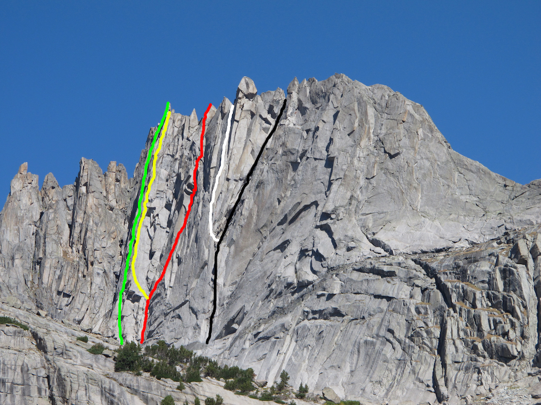 The south face of Wolfs Head, in the Cirque of the Towers in Wyoming's Wind River Range. Green: Green Dragon (III 5.11 PG-13, Gust-Kimbrough, 2017). Yellow: Brass Monkey (III 5.12c, Gust-Kimbrough, 2017). Red: Red Cloud (III 5.12b, Collins-Gust, 2012). White: White Buffalo (III 5.12d, Collins-McBride, 2005). Black: South Face (5.8, Beckey-Fuller, 1966). The classic East Ridge (5.6, Buckingham-Plummer, 1959) follows the skyline.