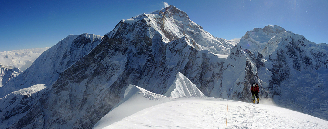 Alexey Lonchinsky moving up to the summit of Phungi Himal for the second time before beginning the descent of the west ridge. The large summit in the center is Manaslu (8,163m), the distant multi-summited peak to the right Ngadi Chuli (Peak 29, 7,871m), and just in front of this is Thulagi (7,059m).