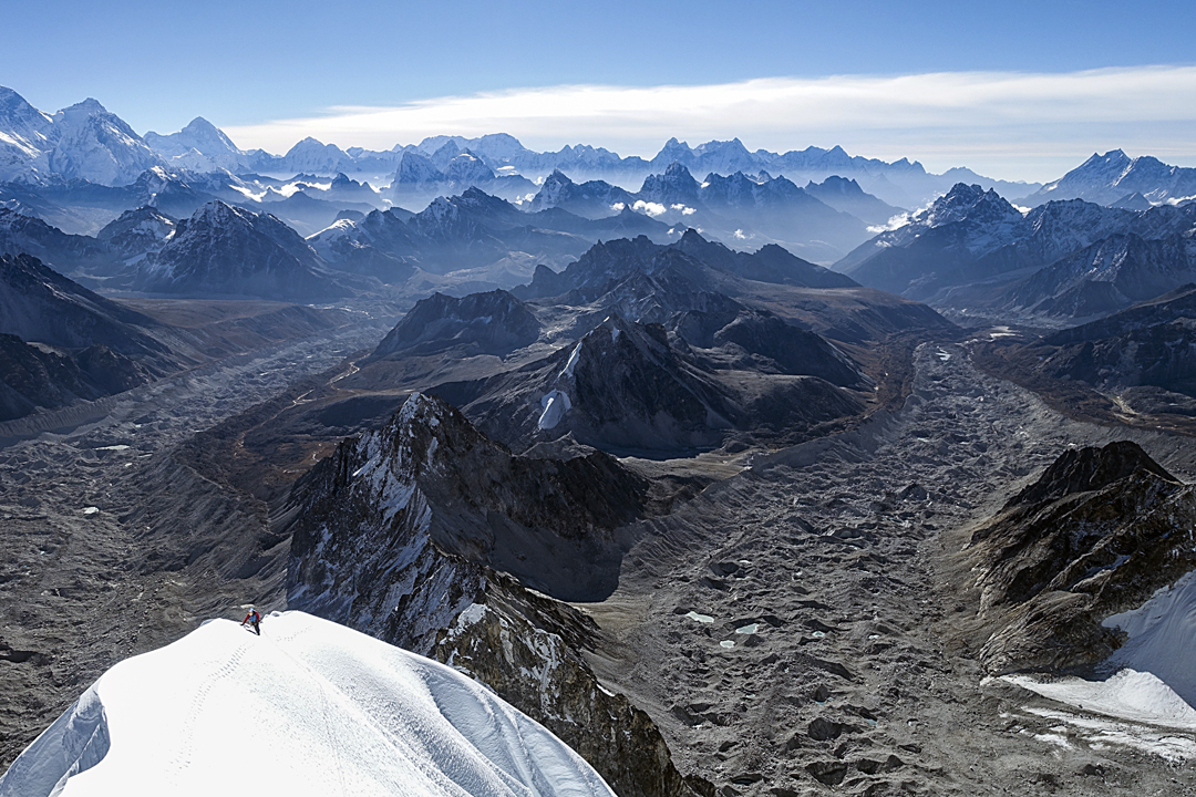Pierre Sancier on the summit ridge. Behind him the continuation of the southeast ridge ends at Peak 5,777m. To the left the Lunag Glacier flows into the Nangpa Glacier; to the right is the Pangbuk Glacier. The Everest-Lhotse group and Makalu are on the far left.