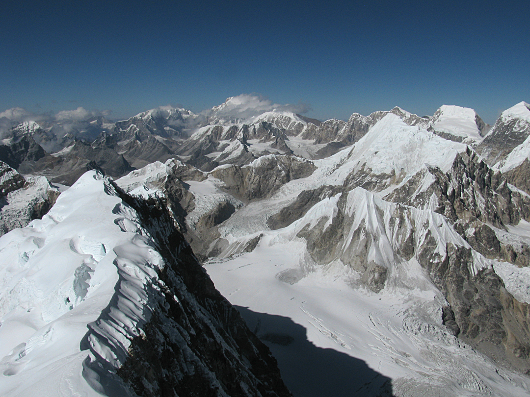 Looking down to the last flat area on the northwest ridge from the summit of Kyungka Ri. The glacier to the right flows east into the upper Langtang Glacier, and the low rock and snow pyramid peak visible at its northern head is Dragmorpa Ri (6,185m, see AAJ 2015). The higher snowy pyramid behind is Chusumdo Ri (6,602m).