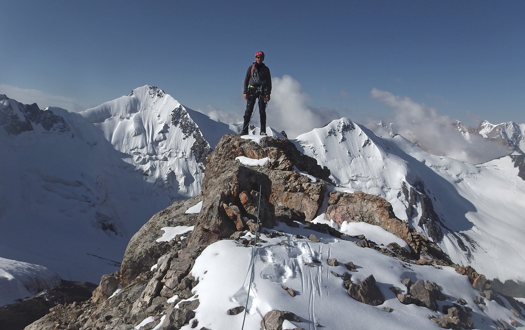 Neil Cox on the summit of Pik 4,722.3m (4,727m GPS) with Pik 4,785.5m behind and to the right, and unclimbed (but attempted in 2017) Pik 4,898.7m to the left.