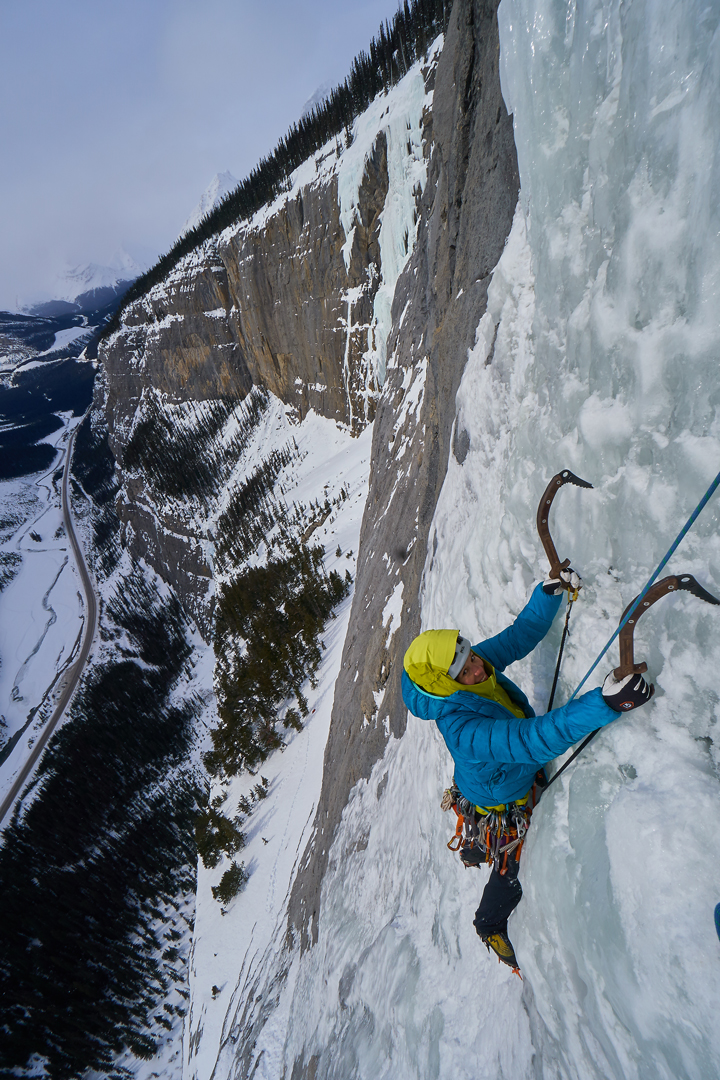 A smiling Ixchel Foord arrives at the first belay during the first ascent of the Lynx (130m, WI5, Walsh, Ixchel Foord, Cecilia Buil), high above the Icefields Parkway, with the Upper Weeping Wall in the background behind her.