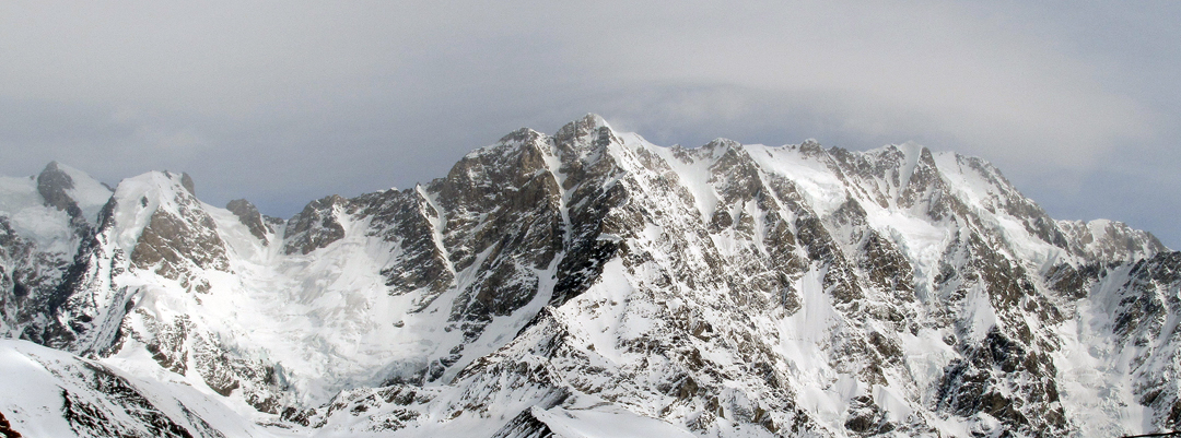 The Shkhara Massif—part of the Bezengi Wall—from the southwest. Shkhara West, in the center of the picture, appears as the highest point, but the main summit of Shkhara is near the right end of the ridgeline. The curving southwest couloir of Shkhara West is obvious in this photo.