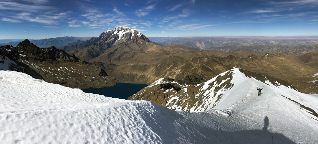 Brian Houle on the summit (south) ridge of Cerro Arkhata, completing the first ascent of the Keep on the southeast face. Laguna Arkhata is visible in middle distance, while in the background is the northwest side of the Illimani massif (and in the very far distance left the Quimsa Cruz).