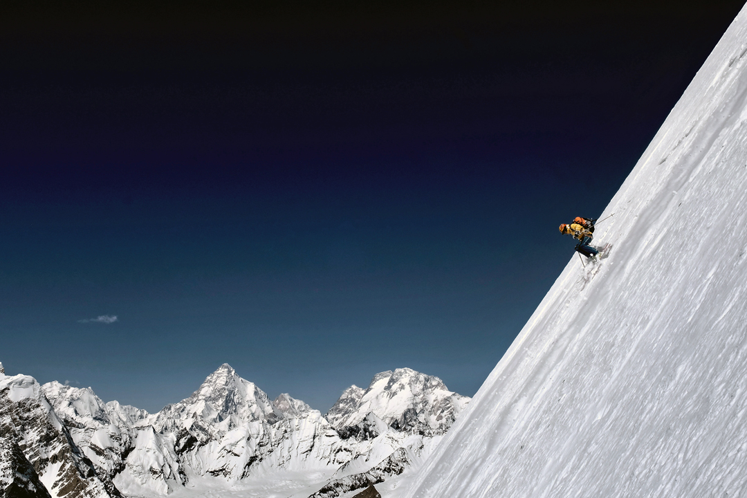 Tiphaine Duperier skiing high on the northwest face of Laila with, from left to right, K2, Skyang Kangri, Broad Peak North, Middle and Main.