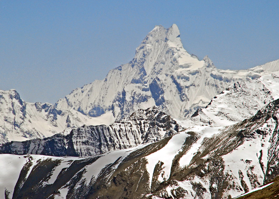 A telephoto from Nagoru Far East looking southwest at Machhapuchhare (6,993m). Despite rumors of an unauthorized ascent, it's most likely that the closest climbers have come to this sacred summit is about 40 vertical meters below the north top. This occurred in 1957 on the only recorded serious attempt: David Cox and Wilfred Noyce (U.K.) were stopped near the top of the steep triangular face below the right-hand (north) summit, when faced with hard polished ice and snowfall.