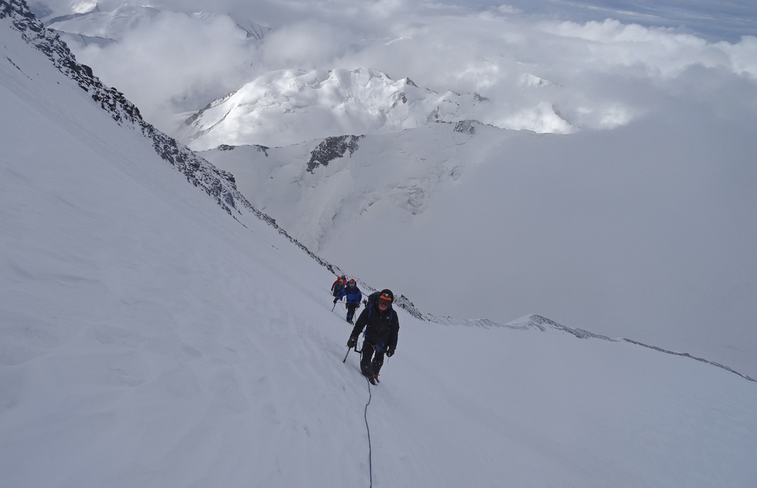 On summit day during the first ascent of Rangston Gyathok, traversing from the southwest ridge (behind) to the couloir on the upper west face.