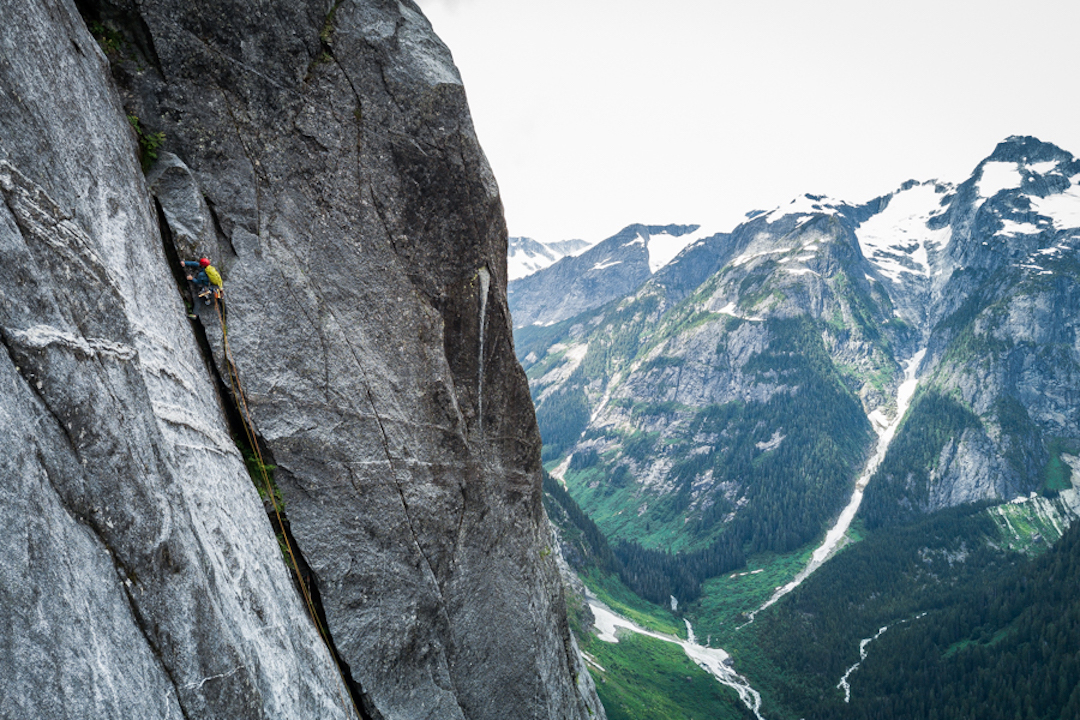 Chris Kalman forges up a vegetated wide crack, 800 meters up the Northwest Passage.