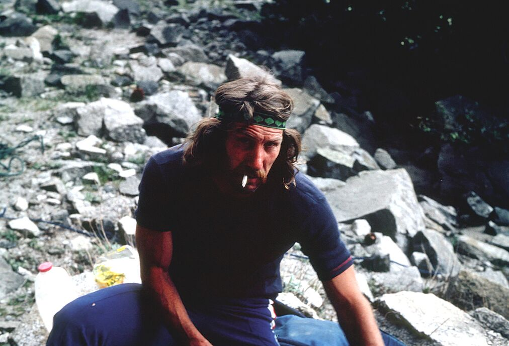 Jim Bridwell at the base of Sea of Dreams on El Capitan, having just fished a baby rattlesnake out from under a rock where his gear was cached.
