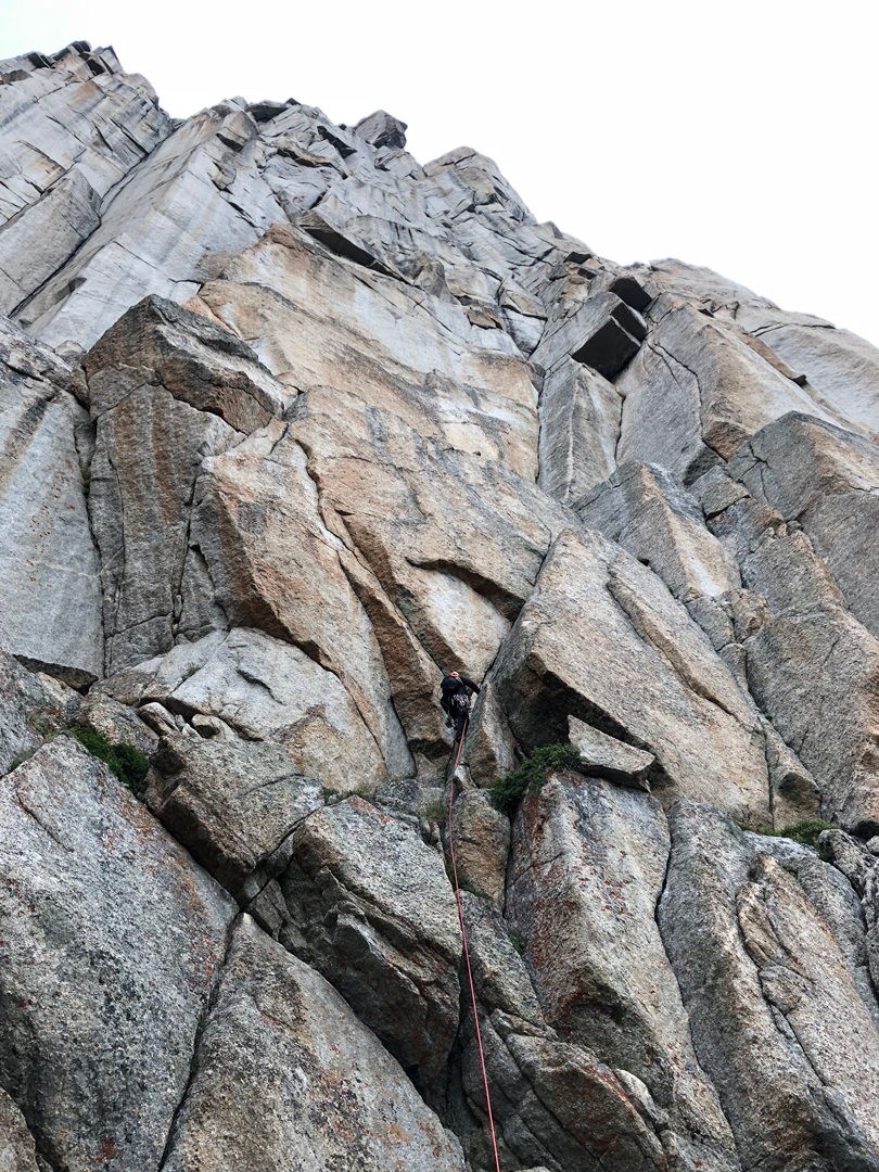 Justin Loyka making his way up the headwall beneath myriad enticing options while establishing Noble Beast (1,300', 5.11 C1) on Cathedral Peak in the Wind River Range.