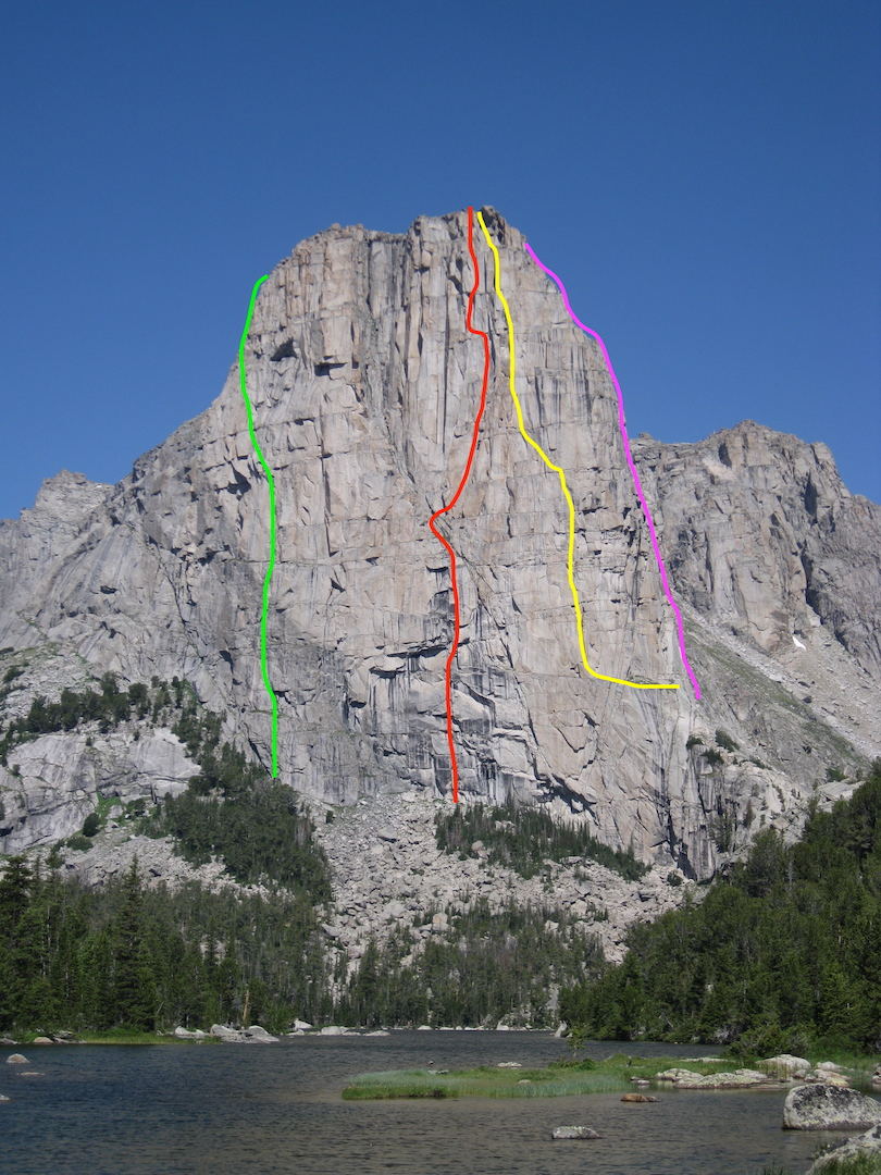 The east-facing wall of Cathedral Peak, above Cathedral Lake in the eastern Wind River Range. Green line: approximate line of South Tower Direct (McNamara-Rowell, 1999). Red: Noble Beast (Kalman-Loyka, 2018). Yellow: Orion's Reflection (Beckey-Kanzler, 1979). Pink: approximate line of Flight of the Golden Camalot (Hunt-Keith, 2001).
